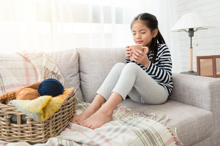 cute Asian kids enjoy and smell hot chocolate happy to drink it sitting on the floor in the living room at home