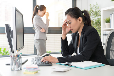 two Asian businesswoman lady got a headache painful of the problem from useless marketing strategy and brainstorming like a team. Stock Photo