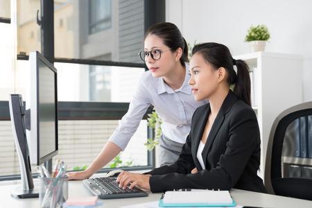 Projektmanagerin arbeitet mit ihrer Untergebenen und überlegt, wie sie das neue Designprojekt für das Marketing im Büro präsentieren kann. Standard-Bild