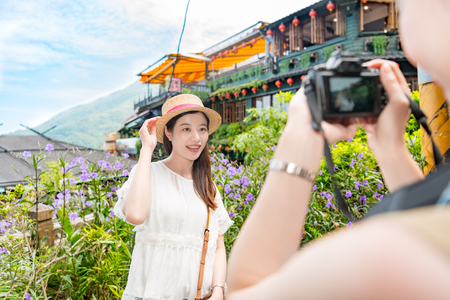 girls friends help to take holiday travel photos for each other, famous Amei tea house landmarks on the background. 写真素材 - 98854903