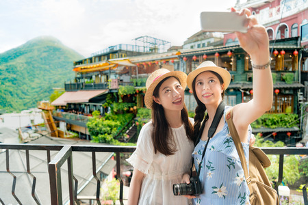 two beautiful girls taking selfie photo of famous landmarks Amei tea house of Jiufen Taiwan. Travel holiday vacation concept. Фото со стока - 98855751