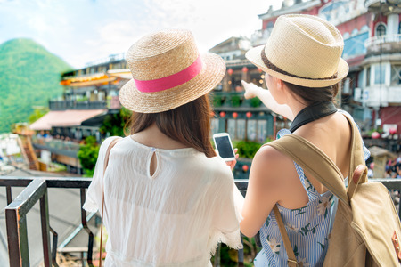 rear view of two beautiful girls visiting famous attractions of Jiufen Taipei Taiwan and pointing the Amei tea house, and checking the information online of the smartphone.