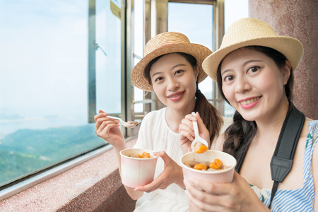 two traveler girls love the famous Taiwan local food on top of Jiufen hill of Taipei city. Stock Photo