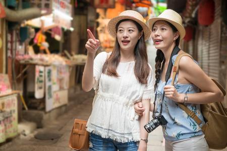 Two beautiful Asian girls pointing and walking on Jiu Fen old street pedlar shop of Taiwan holiday travel. 写真素材 - 98855968