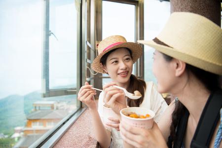 charming Asian girls eating famous yam taro balls on top hill of Jiu Fen of Taipei city Taiwan.