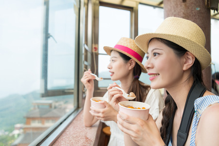 charming Asian girls enjoy the view of the top hill of  Taipei city Taiwan. Eating famous yam taro balls for snacking.