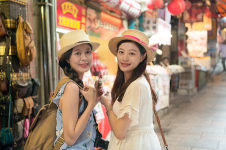 Two Asian girls friends visiting working on Jiufen old street and enjoy eating local food herbal cake and turn back face to camera, holiday travel vacation in Taipei Taiwan. Stockfoto