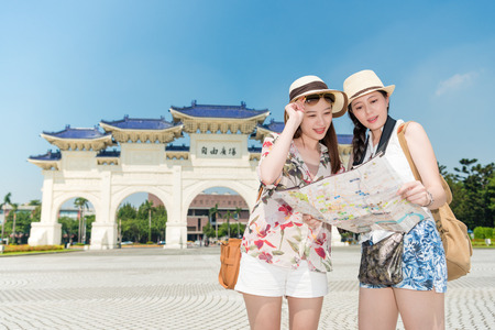 Female backpackers looking up the map to search the correct way in Chiang Kai-shek Memorial Hall. Planning the next destination on map. Translation on decorated archway text