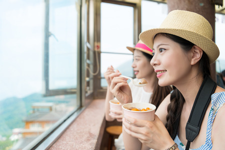 happy two Asian women tourist enjoy have famous local food taro balls in Jiufen of Taipei city, looking out great ocean view from the top of the hill. 写真素材 - 98857079