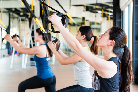 beautiful Asian girl learning using total body resistance exercise TRX for training her slim body pull and look up. Stock Photo