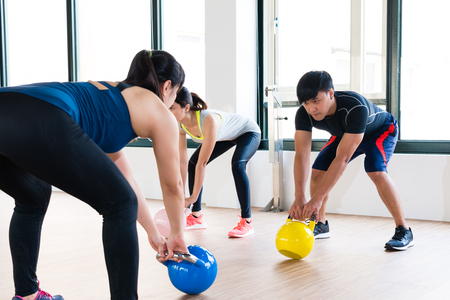 professional fitness coach showing how to workout with kettlebell in front of the group of team learner in the gym. Archivio Fotografico