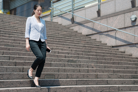 charming business Asian woman walking down on the stair after meeting with her customer.