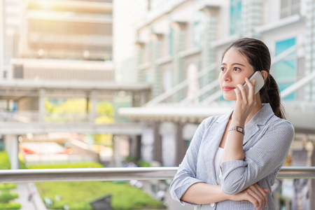 successful office woman answers the phone call from her client and looks away vision standing outside of the office.