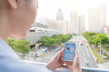 charming woman looking at smartphone air quality index app to know how is the pollution outside of the office on rush hours time. Stock Photo