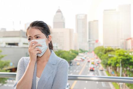 L'affascinante signora dell'ufficio si sente malata e allergica dal cattivo inquinamento dell'aria e indossa una maschera fuori nelle ore di punta. Archivio Fotografico - 98868354