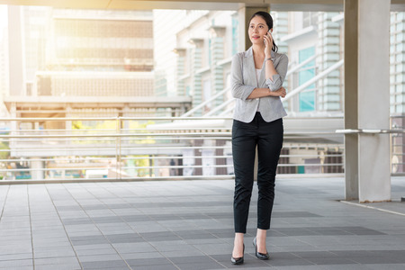 beautiful business woman walking on the flyover outside of the office and talking on the phone call with her client. Foto de archivo