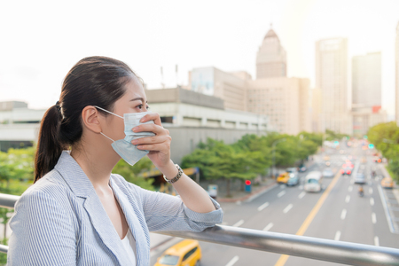 beautiful businesswoman feels allergy from bad air quality pollution and wear a mask standing outside. Фото со стока