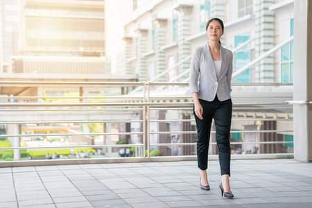 beautiful businesswoman walking on the flyover outside of office to take a rest after work. Stock Photo