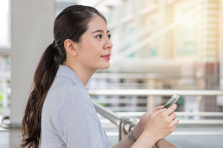 beautiful girl using looking out of future vision and holding a smartphone outside of company office. 写真素材 - 97200028