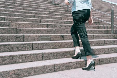 Vista cercana de pie pierna mujer tacones altos caminando en la escalera, concepto de promoción empresarial. Foto de archivo