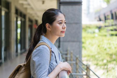 建物の外に立ち、遠くを見て、彼女の将来の計画を考える若い美しいビジネス旅行者。 写真素材