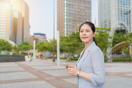 beautiful businesswoman walking on blue sky sunny day withholding her smartphone. Stock Photo