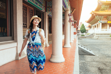 Beautiful asian model happy travel lifestyle. Chinese woman running dancing in the wind of happiness and lust for life. Elegant lady in dress at old traditional temple in China.