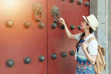 Beautiful asian young woman relaxing on summer holiday by ancient traditional and play knock wooden red door in Chinese temple on China travel destination. Girl tourist in elegant sun dress.