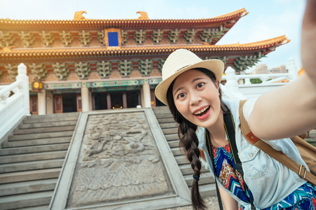 Happy Asian tourist taking a fun selfie at the famous tourist attraction in Beijing, China. Asia summer travel. Young woman taking mobile picture with smartphone at Temple.