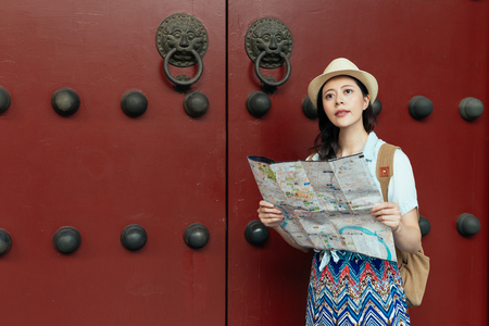 Beautiful asian young woman holding a paper map on summer holiday by the ancient traditional wooden red door in Chinese temple on China travel destination. 版權商用圖片