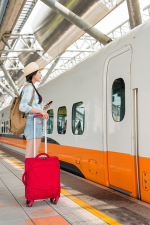 Young Asian travel woman holding a cell phone and suitcase in her hand waiting on the platform of a railway train to arrive stop. Public transport.