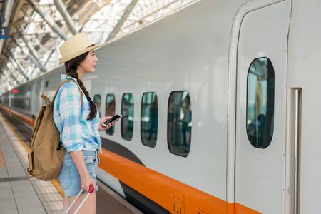 Azjatycki podróżnik czeka na przybycie podróży na peronie. kobieta, stojąca z bagażem na stacji kolei dużych prędkości na Tajwanie gotowa do wyjazdu na wakacje.