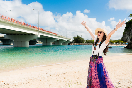 Cheerful young teen girl excitingly raises up her arms. Enjoying this gorgeous natural view of Naminoue Beach, Japan. Good location for summer to play Aside the blue sky and water. Banco de Imagens - 97268838