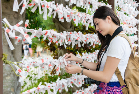 Pretty female backpacker attend wish ceremony at Naminoue Shrine. During her summer vacation, holidays, leisure time. She enjoys her lifestyle.