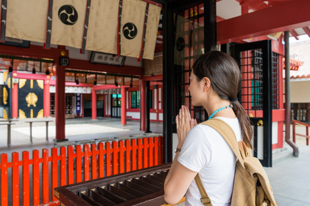 A beautiful young woman spending time in front of incredible of  Naminoue Shrine attraction. Wearing backpack. Summer is coming. Travel journey concept.