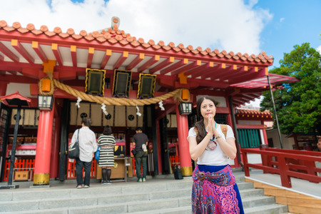 Asian female attends to Naminoue Shrine building enjoying Japanese traditional culture. Making a wish hope for a better future.Traditional travel attraction with blue sky concept. 版權商用圖片