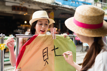 Travelers writing their wishes on the colorful sky lanterns on Shifen Old Street section of ping si District. Translation on sky lanterns text good fortune and wealth. Stockfoto