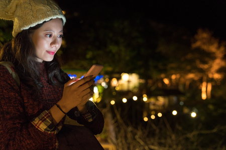 young japanese girl texting to her friend at camping outdoor mountain at night time. Stock Photo