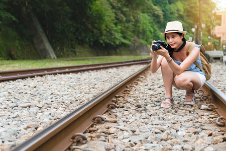 A young asian beautiful traveler in casual look crouching on the railway and using camera taking photos in sunny summer day. Stock Photo