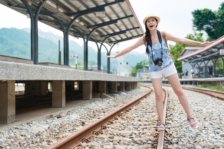 Beauty young woman walking on railway track balancing with her arms extended. The railroad is in a train station. The woman has a casual look and having fun in sunny summer day.