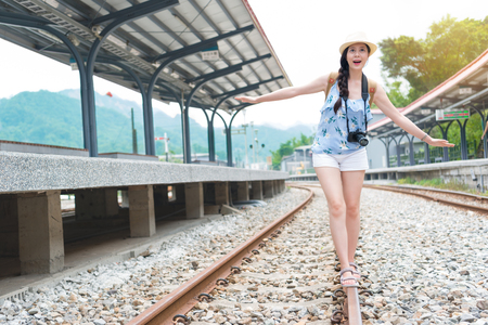 Beautiful young woman walking in balance on railway tracks. The railroad is in a train station. The woman has a casual look.