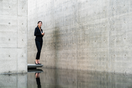 Full length portrait of young pretty business woman using cell phone over gray concrete background.