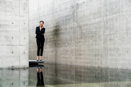 happy young asian businesswoman talking on the phone standing outside of office. Stock Photo