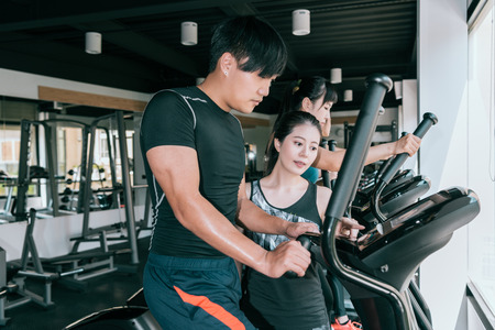 man working out on elliptical machine in gym with his personal trainer. Healthy lifestyle fitness concept. Stock Photo
