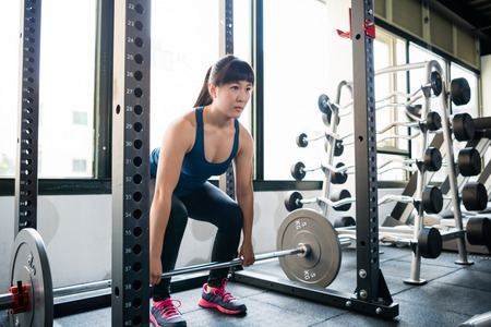 Asian athletic young woman doing deadlift exercise with barbell in the smith machine. 스톡 콘텐츠