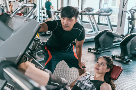 Personal trainer helps his female client working at leg press in the gym. Concept of indoor fitness healthy lifestyle.