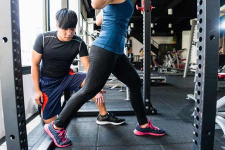 Woman doing lunge exercise in modern fitness center with assistance of her personal trainer. Banco de Imagens