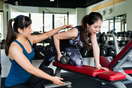 Woman strength training lifting dumbbell weights in bent-over one-arm dumbbell row in fitness center. Her personal trainer is helping her.
