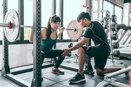 バーベルでスクワットをしている女性。パーソナルトレーナーは、ジムでスミスマシンで彼女の屈曲筋肉を助けます。