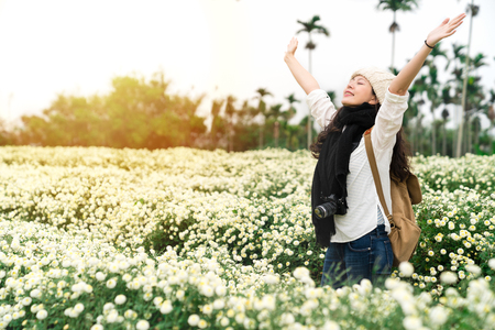 A freedom woman in a casual look raised her arms up in a meadow full of white flowers. Enjoying the fresh air.